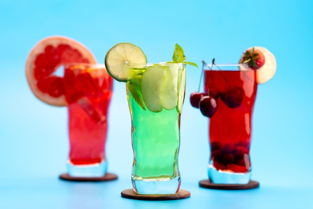 Вид спереди свежие фруктовые коктейли с кусочками свежих фруктов ледяное охлаждение на синем, напиток сок коктейль фруктовый цвет
