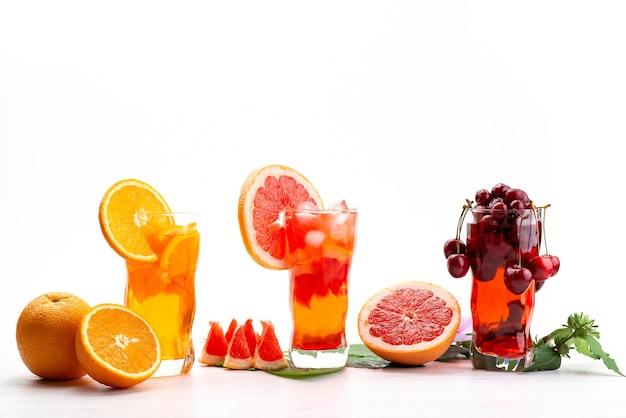 Вид спереди свежие фруктовые коктейли с кусочками свежих фруктов ледяным охлаждением на белом, напиток сок коктейль фруктовый цвет