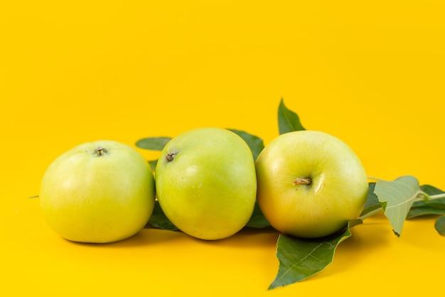 Вид спереди свежие зеленые яблоки, спелые и сочные на желтом, фруктовом летнем цвете