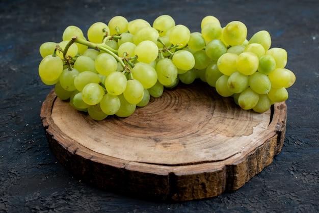 Вид спереди свежий зеленый виноград кислый, сочный и спелый на деревянном столе и темный фон фрукты спелые растения зеленые