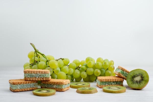 正面の新鮮な緑のブドウの酸っぱいジューシーでクッキーとキウイのまろやかな白い背景のフルーツ熟した植物緑