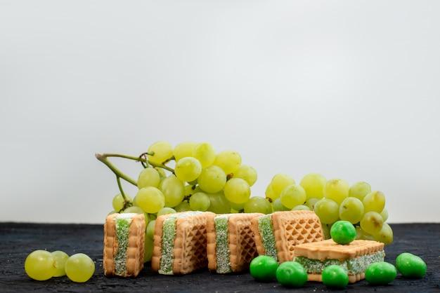 正面の新鮮な緑のブドウの酸っぱいジューシーでまろやかな、暗い背景の果物熟した植物のクッキーとまろやか