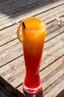 正面の新鮮なオレンジカクテル、木製の机の上の長いグラスの中の氷とストローでカクテルジュースを飲む