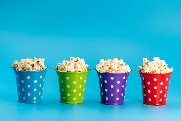 Свежий попкорн, вид спереди, в разноцветных корзинах на синем, кукурузные закуски из кино