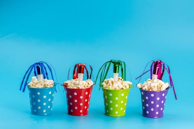 Свежий попкорн, вид спереди, в разноцветных корзинах на синем, семечки для снеков из кино