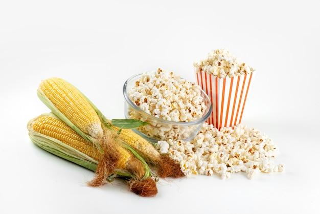 Свежий попкорн, вид спереди с желтыми сырыми зернами на белом, цвет фильма о закусках