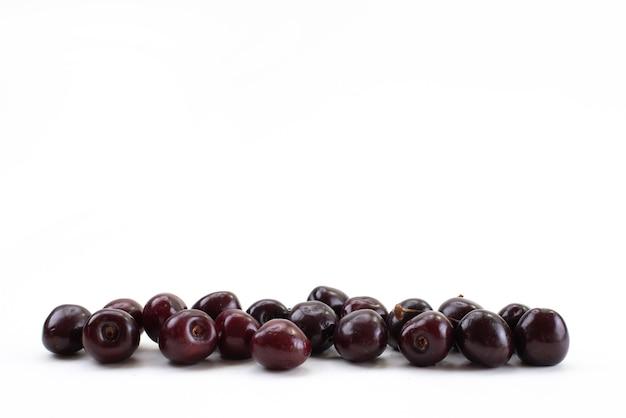 Вид спереди свежие красные вишни, спелые, кислые и сочные на белом, спелом цвете фруктов