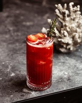 正面の新鮮な赤いカクテルコールドで美味しいグラスの中の飲み物ジュースフルーツと暗い表面