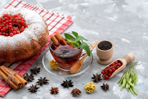 正面の新鮮な赤いクランベリーの酸味とまろやかな丸いケーキティーとシナモンホワイトデスクの新鮮な色