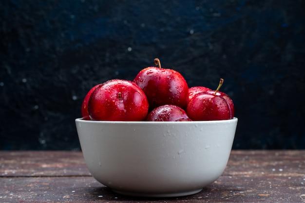 Вид спереди свежие красные сливы, спелые и спелые внутри белой тарелки на деревянном столе, фруктовый сок из мякоти