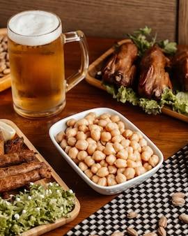 Вид спереди жареное мясо с пивом и орехами на коричневом деревянном столе.