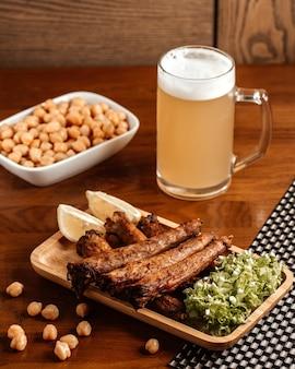 茶色の木製の机の上のビールレモンと豆と揚げ肉の正面図スナックナッツ食品食事