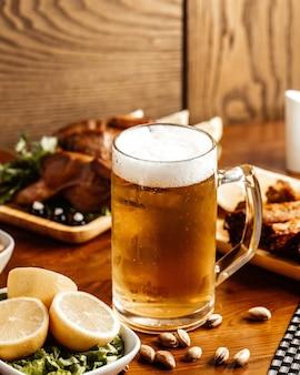 Вид спереди жареное мясо с пивом, лимоном и орехами на коричневом деревянном столе.