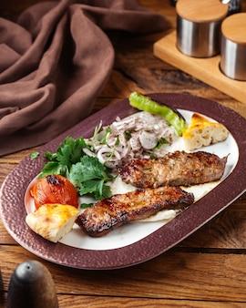Вид спереди жареное мясо с зеленью и помидорами внутри тарелки на коричневом деревянном столе еда еда мясо овощ