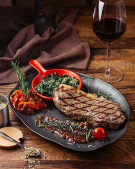 Вид спереди жареное мясо с зеленью внутри темной тарелки на коричневом деревянном столе.