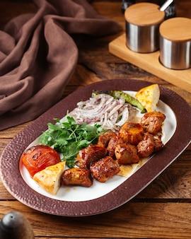 Вид спереди жареное мясо с зеленью внутри тарелки на коричневом деревянном столе еда еда мясо овощ
