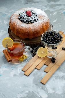 Фруктовый торт, вид спереди, восхитительный и круглый, со свежими синими ягодами и чашкой чая на ярком бисквитном сладком сахаре.