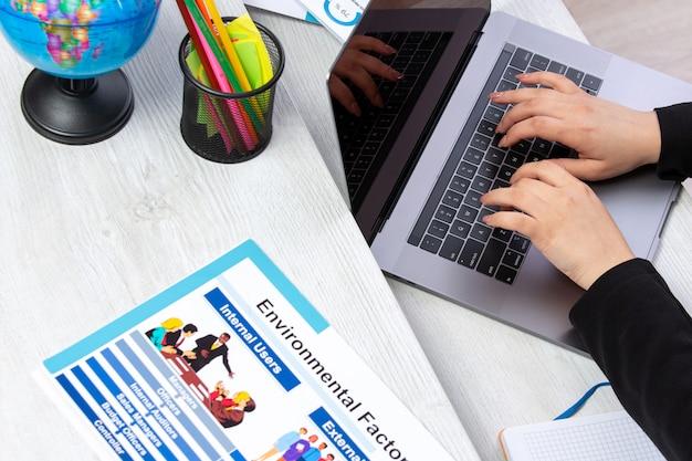 スケジュールとグラフィックスを備えたテーブルの前でラップトップを使用し、ラップトップの仕事のビジネス活動を使用する正面の女の子