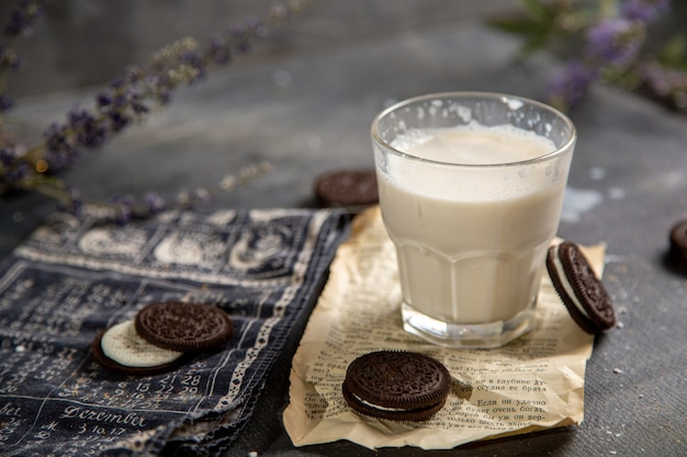 Стакан молока с вкусным шоколадным печеньем на сером столе, сахар, сладкое печенье, молоко, вид спереди