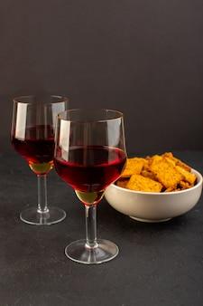 暗闇の中でプレート内のチップスと一緒にワインの正面図グラス