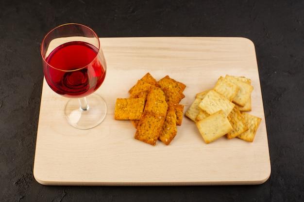 木製の机の上の異なるチップスと一緒にワインの正面図グラス