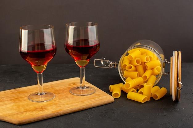 Бокалы с вином на коричневом деревянном столе и сырая итальянская паста на темном фоне