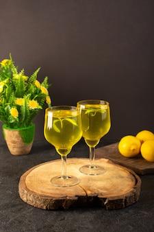 Очки спереди с соком лимонного сока внутри прозрачных стаканов вдоль целого лимона и цветов на коричневом деревянном столе и сером фоне коктейльного лимонного напитка