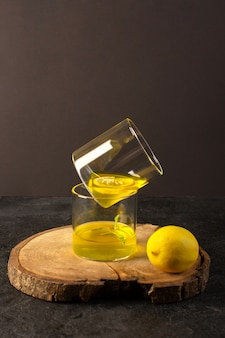 Очки спереди с соком лимонного сока внутри прозрачных стаканов вдоль целого лимона на коричневом деревянном столе и сером фоне коктейльного лимонного напитка