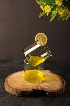 Очки спереди с соком лимонного сока внутри прозрачных стаканов вместе с цветами на коричневом деревянном столе и сером фоне коктейль лимонный напиток