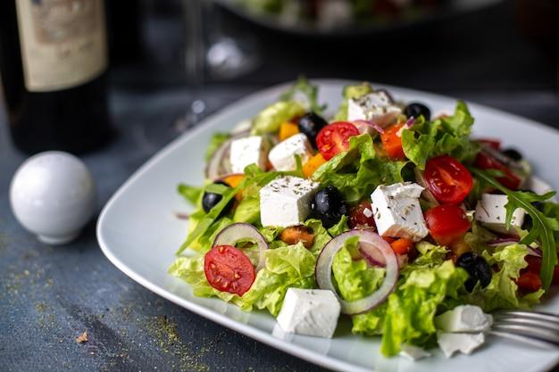 Вид спереди греческий салат нарезанный овощной салат с помидорами, огурцами, белым сыром и оливками внутри белой тарелки с витаминами