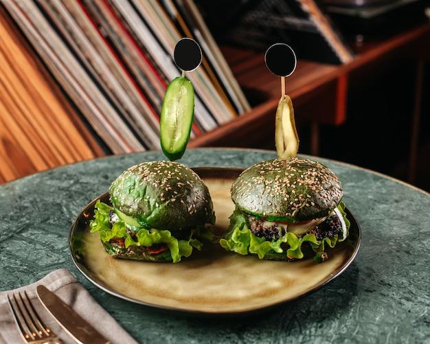 緑の机の上の丸皿の中にグリーンサラダと正面の緑のハンバーガー