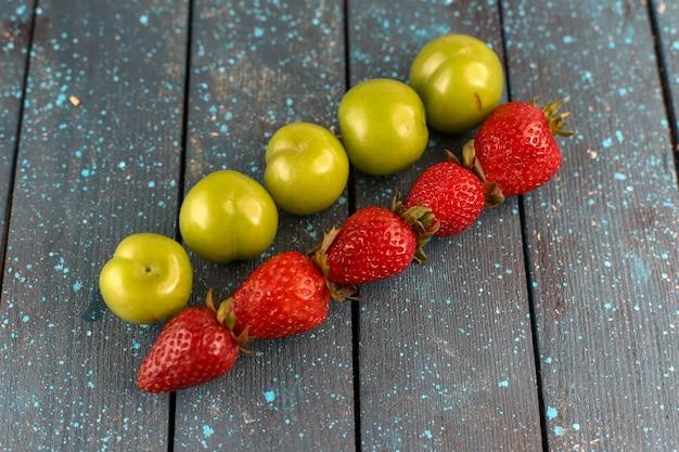 Спелые и кислые зеленые алычи и свежая красная клубника, вид спереди