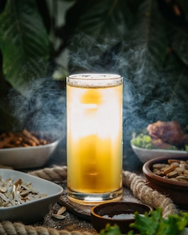 Вид спереди ледяной коктейль в длинном стакане с блюдами и орехами на столе пить сок коктейль ледяное мясо
