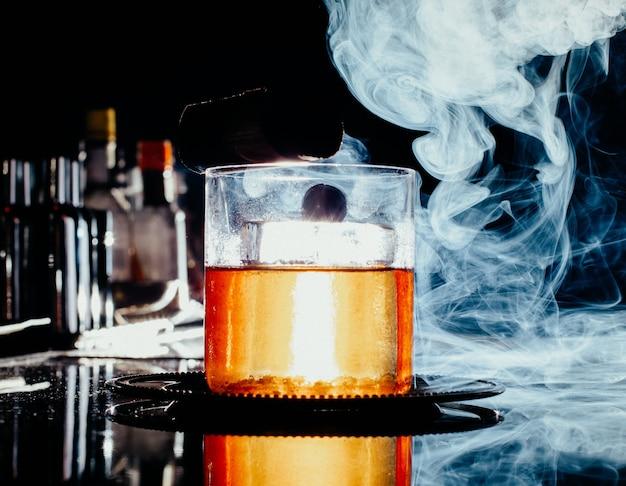 暗いガラスの机の上の煙と小さなガラスの中の正面のアイスドリンク