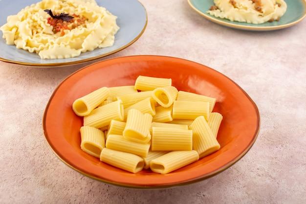 Итальянская паста, вид спереди, вкусная и соленая на круглой оранжевой тарелке на розовом столе