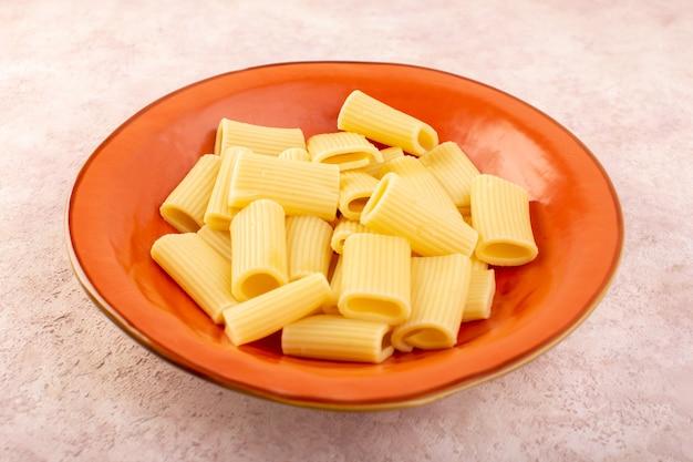 ピンクの机の上の丸いオレンジプレートの内側で美味しい塩漬けのイタリアンパスタの正面図