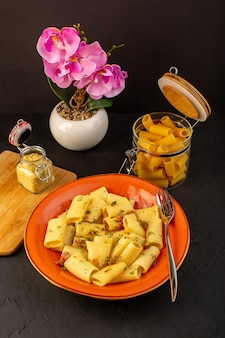 正面図のイタリアンパスタは、丸いオレンジプレートの内側においしい塩を入れて調理し、デザインされたカーペットと暗い机の上に花をつけます
