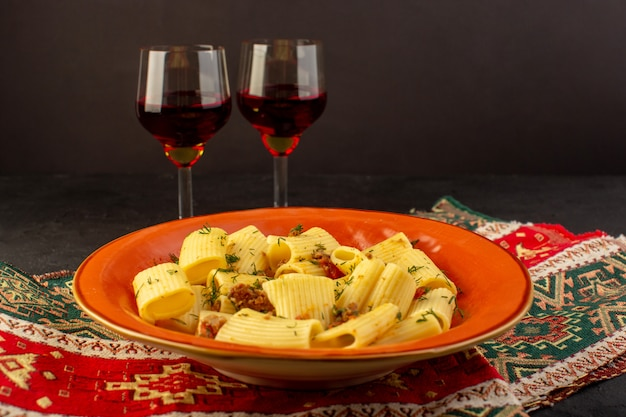 Итальянская паста, вид спереди, приготовленная со вкусом, посоленная на круглой оранжевой тарелке с бокалами вина на ковре и темном столе
