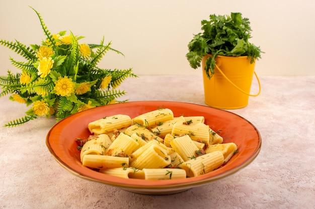 전면보기 이탈리아 파스타는 말린 채소로 맛있게 요리하고 분홍색 책상에 꽃과 함께 둥근 주황색 접시 안에 소금에 절인 것입니다.
