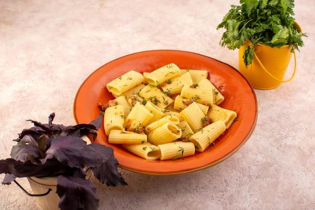 正面図のイタリアンパスタは乾燥した緑で美味しく調理され、ピンクの机の上に花のある丸いオレンジプレートの内側に塩漬け