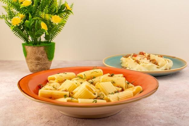 Итальянская паста, вид спереди, вкусно приготовленная с сушеной зеленью и соленая внутри круглой оранжевой тарелки с цветком на розовом столе