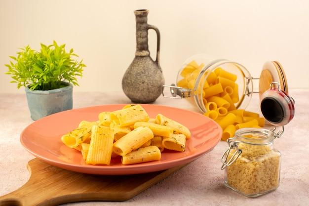 Итальянская паста, вид спереди, вкусная еда внутри розовой тарелки вместе с цветком и сырой пастой на розовом