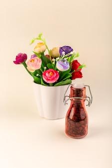 ピンクのテーブルコーヒー色の花の種にコーヒーと花が付いている正面図瓶