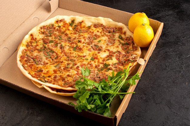 Тесто lahmacun спереди с мясным фаршем, зеленью и лимоном в бумажной коробке, вкусная выпечка