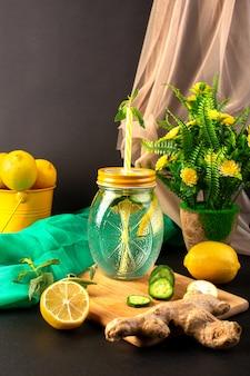正面のレモンカクテルグラスカップの内側に新鮮な冷たい飲み物をスライスし、暗い背景のカクテルドリンクフルーツの花と一緒にレモンキュウリ