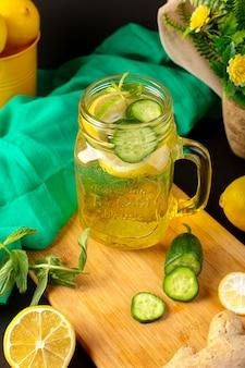 Вид спереди лимонный коктейль свежий прохладный напиток внутри стеклянной чашки нарезанный и целые лимоны огурцы вместе с цветами на темном фоне фруктовый напиток коктейль