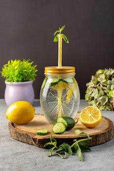 Вид спереди лимонный коктейль свежий прохладный напиток внутри стеклянной чашки нарезанные лимоны огурцы солома на деревянный стол и серый фон коктейль напиток фрукты