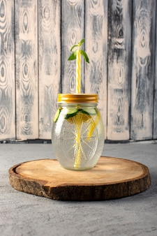Вид спереди лимонный коктейль свежий прохладный напиток внутри стеклянной чашки нарезанный лимон соломы на деревянный стол и серый фон коктейль фруктовый напиток