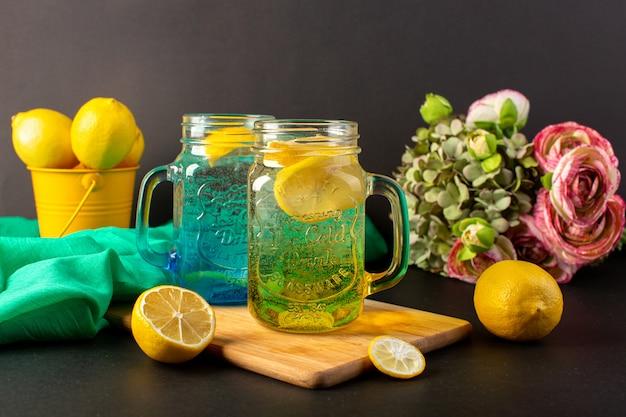 正面のレモンカクテルグラスカップの内側に新鮮な冷たい飲み物と暗い背景のカクテルドリンクフルーツの花とレモン全体