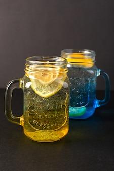 Вид спереди лимонный коктейль свежий прохладный напиток внутри стеклянных чашек нарезанный лимон на темном фоне коктейль напиток фрукты